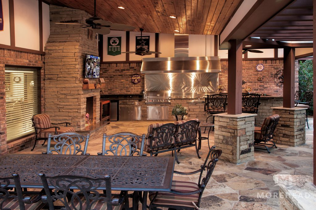 Sheltered outdoor kitchen with fireplace and eating area