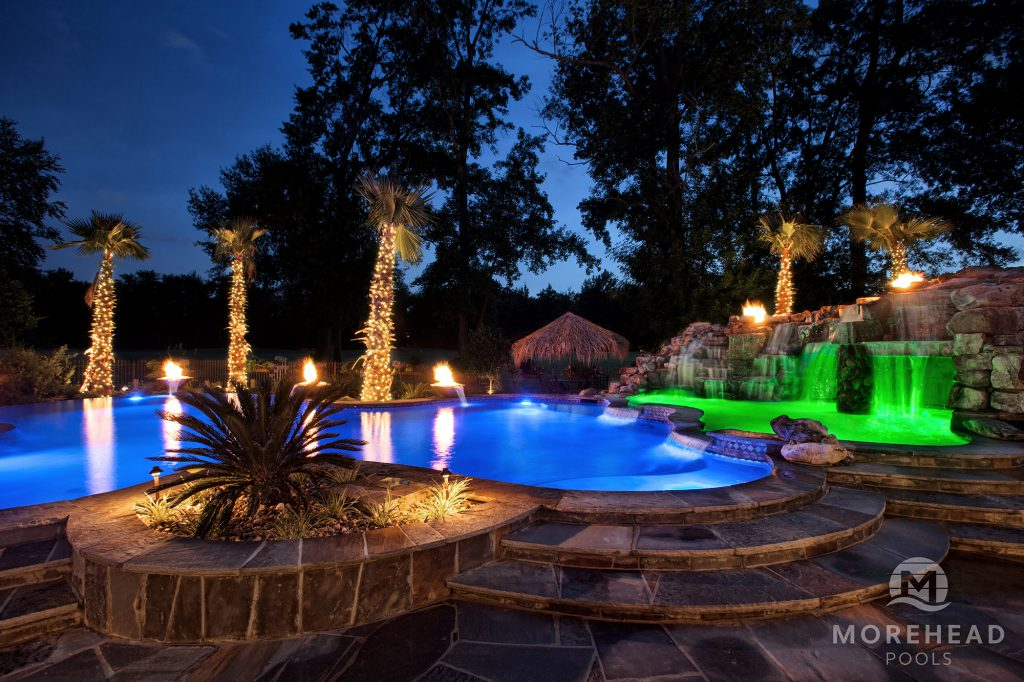 Luxury pool at night with blue and green lights