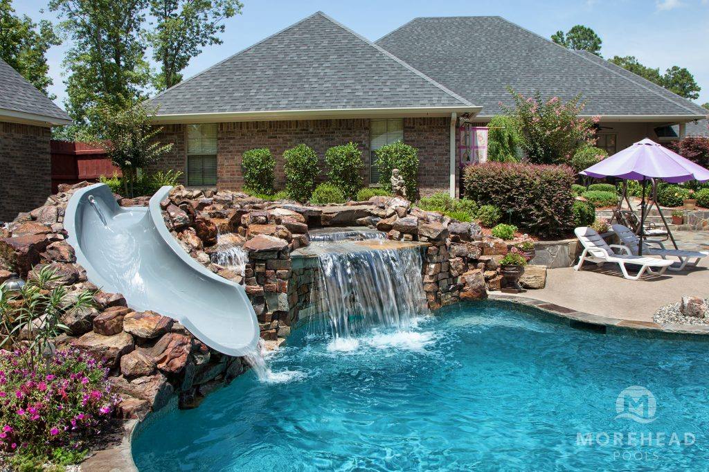 Luxury swimming pool with slide and rock waterfall