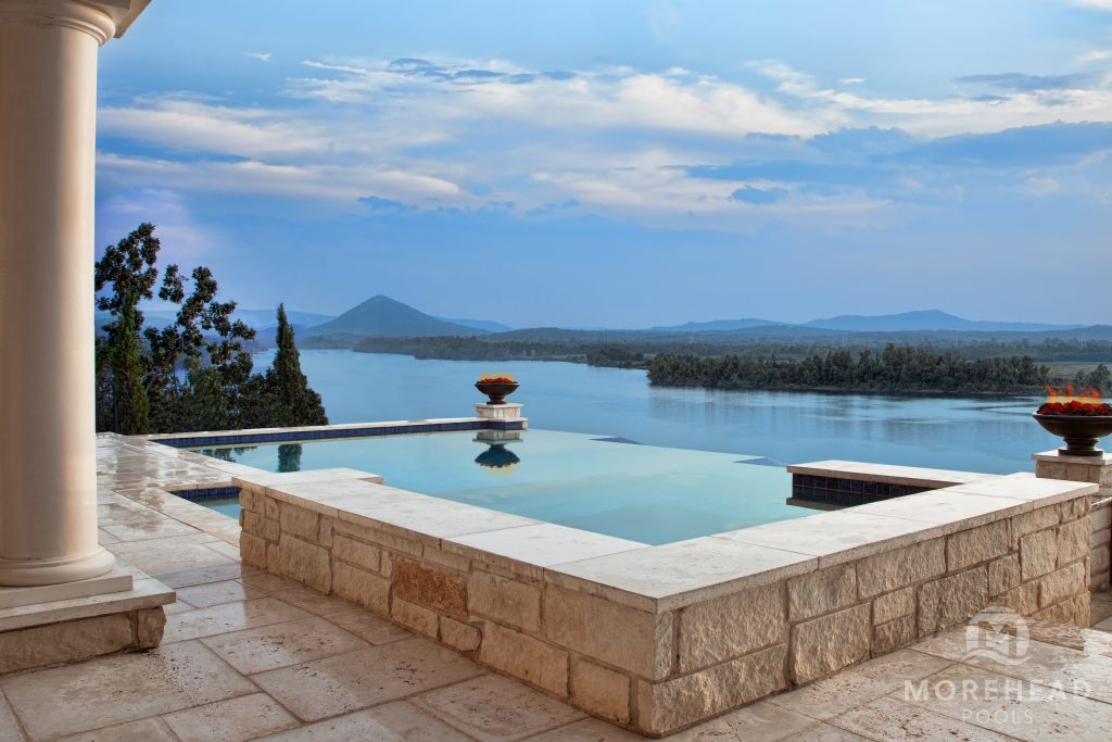 Infinity pool overlooking beautiful background with mountains